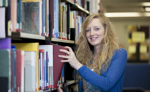 Student taking book from shelf