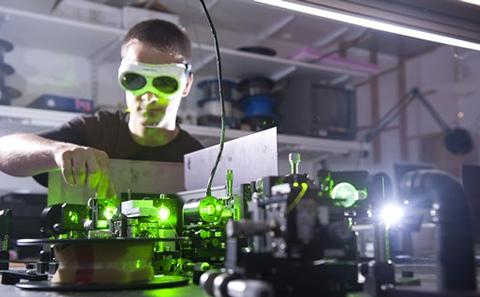 Worker with lasers wearing safety glasses