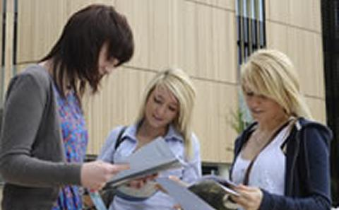 Students looking at University events schedule.