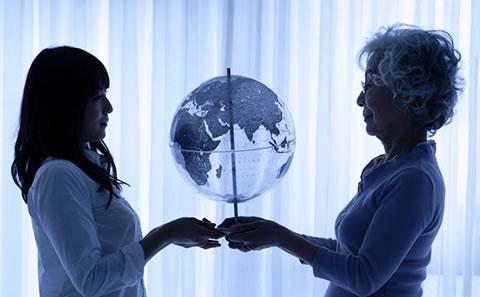Two woman holding up a globe of the world