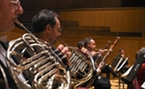 Musicians in orchestra pit playing horn instruments