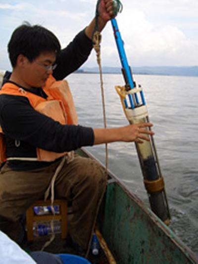 Researcher Enlou Zhang examines at a core sample lifted from the bed of the lake
