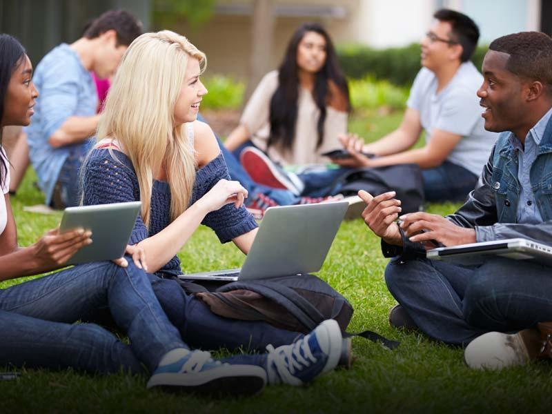 Students with laptops sitting on a lawn