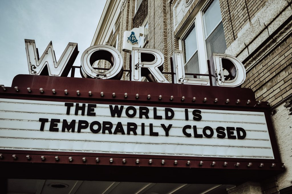 The image shows a cinema sign saying that the world is temporarily closed