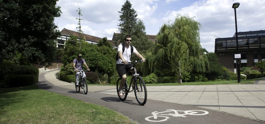 Two cyclists cycling in the University of Southampton's Highfield Campus.