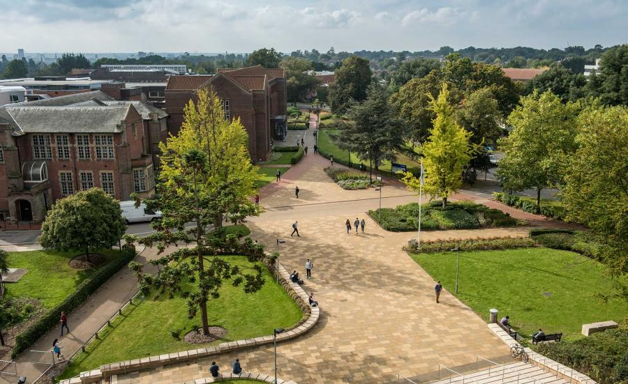 Aerial view of campus buildings, trees and courtyard area on a sunny day.