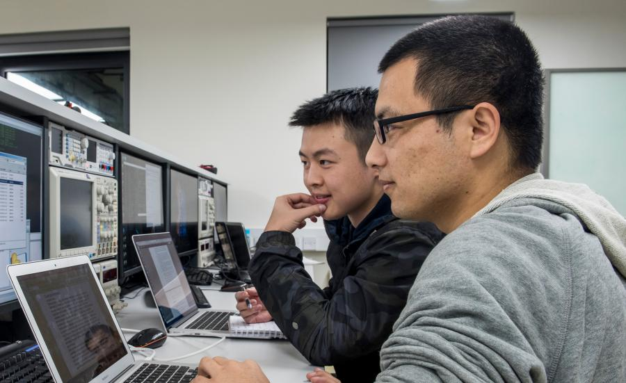 Two male computer science students sitting and looking into their computer