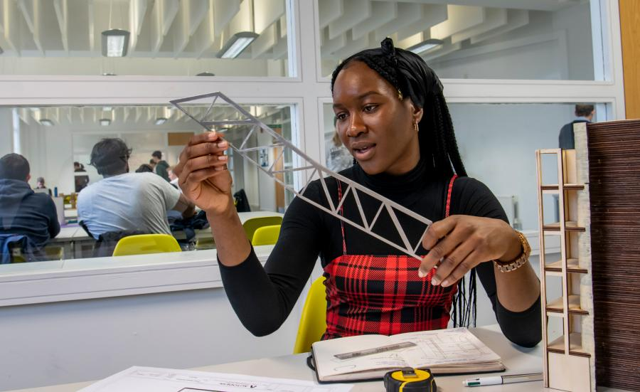 Female undergraduate civil engineering student holding a model of a bridge