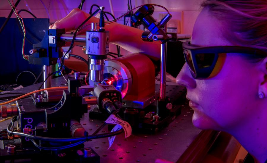 Female photonics degree student wearing glasses and staring into machine