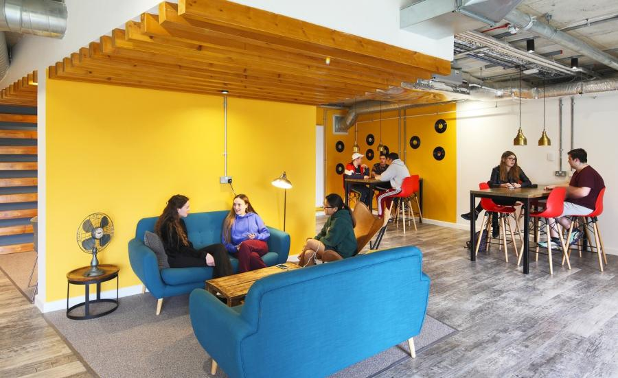 Students talking and relaxing on vibrant furniture in a brightly coloured common room.
