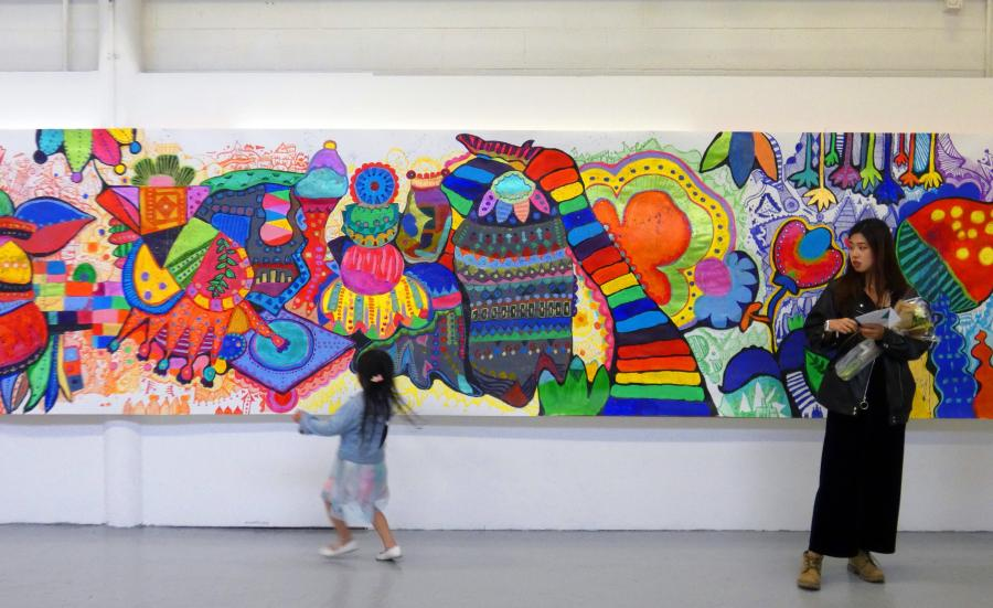 A student standing in front of a colourful mural which covers an entire wall at Winchester School of Art