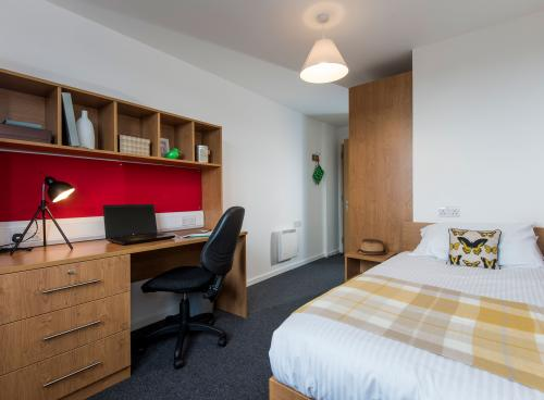 A modern student bedroom with white walls, wooden desk and neatly made double bed.