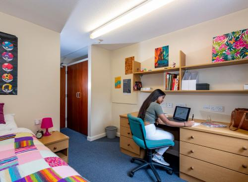 Student working at desk in bright bedroom decorated with colourful posters. A bed with colourful sheets can also be seen.