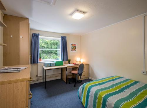 A large student bedroom. The room contains a double bed with striped covers, a large desk, a wooden wardrobe and chest of drawers.