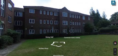 Three storey, red brick accommodation building with a grassy area in front.