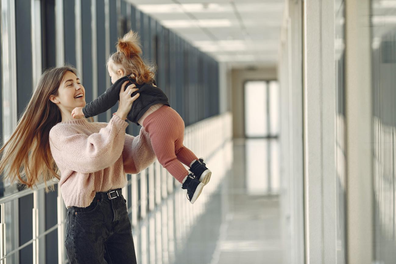Young student spinning her daughter in a corridor.