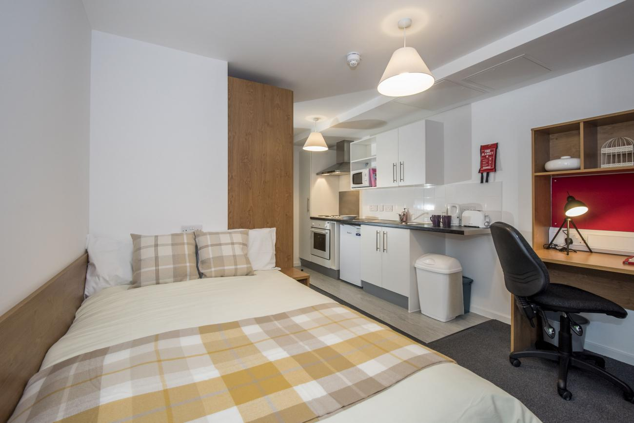 A modern studio flat showing bed, desk and kitchenette.