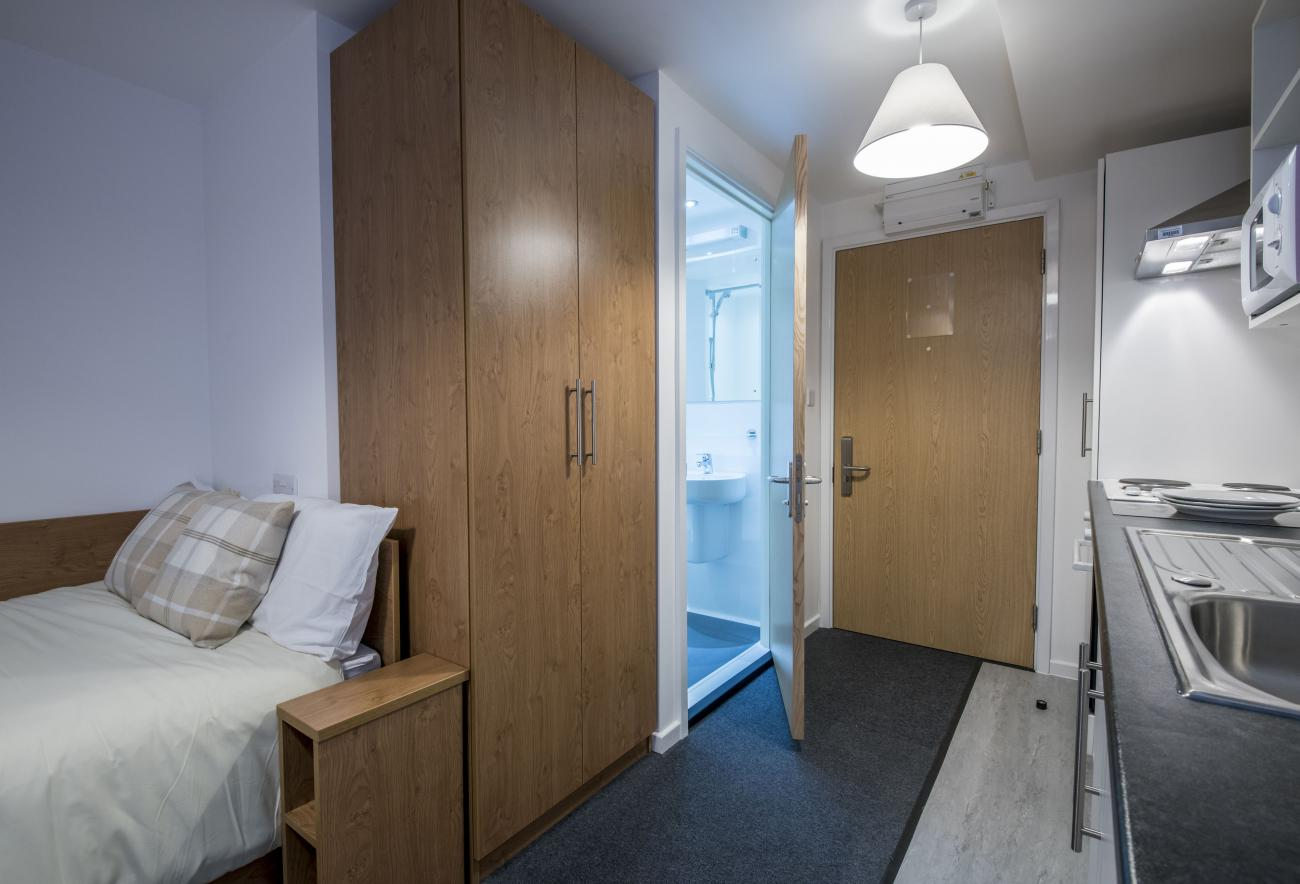 A modern studio flat showing bed, kitchenette and entrance to bathroom.