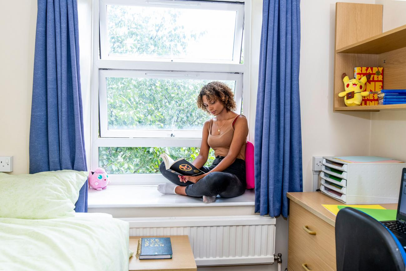 A student sits reading a book beside an open window. A desk and bed can also be seen in the room.