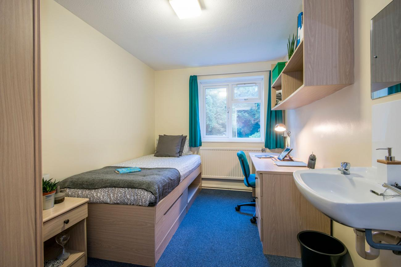 A bright, tidy student bedroom with desk, wash basin and neatly made bed. An open window lets light into the room.