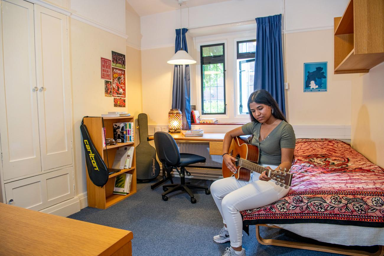A student plays a guitar while sitting on a bed in a bedroom. In the background, shelves and a desk with books can be seen.