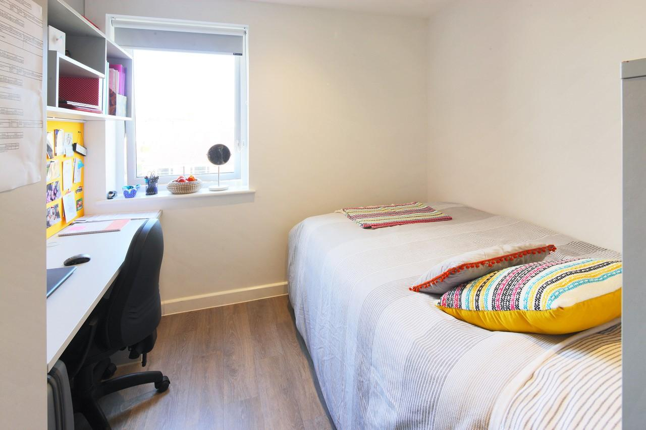 Student bedroom with single bed, large desk area and office chair. The floor is wooden laminated and a large window lets in light.