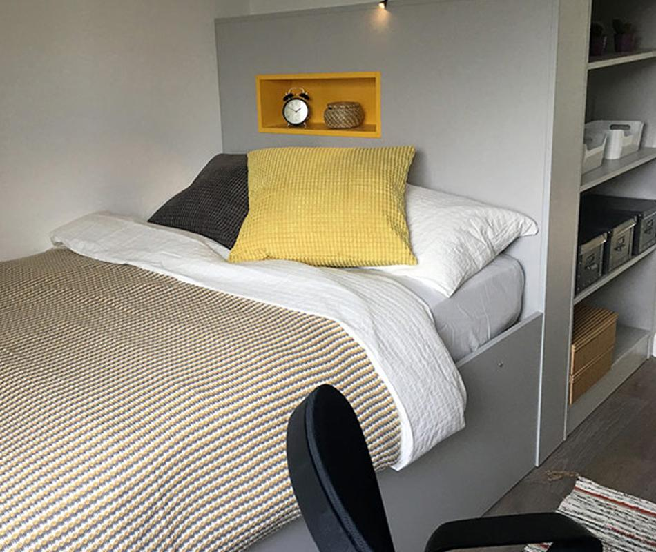 A single bed in a student bedroom. It is neatly made with striped covers and yellow and blue pillows. Shelving with books can be seen in the background.