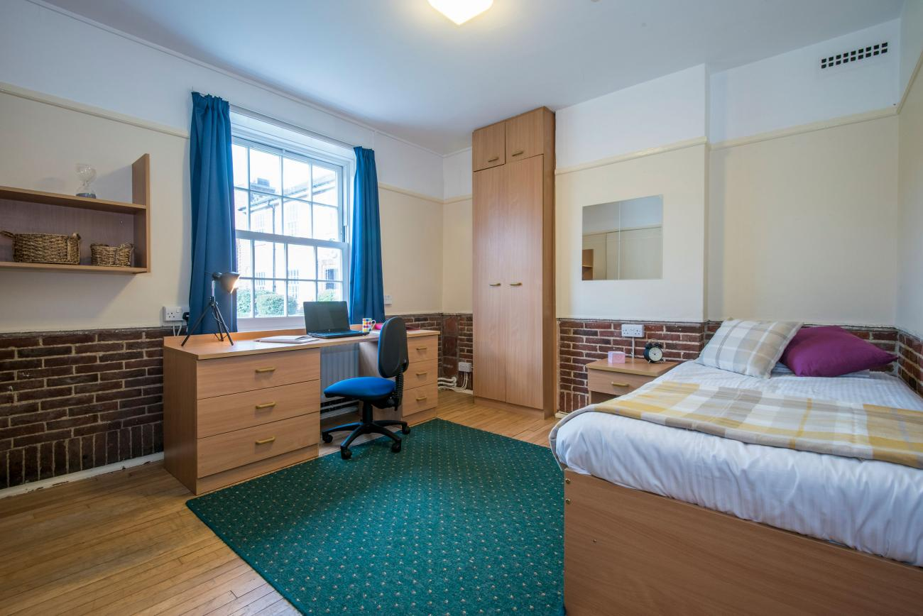 A spacious student bedroom with double bed, green rug on a wooden floor and large desk. Light streams in through a large window.