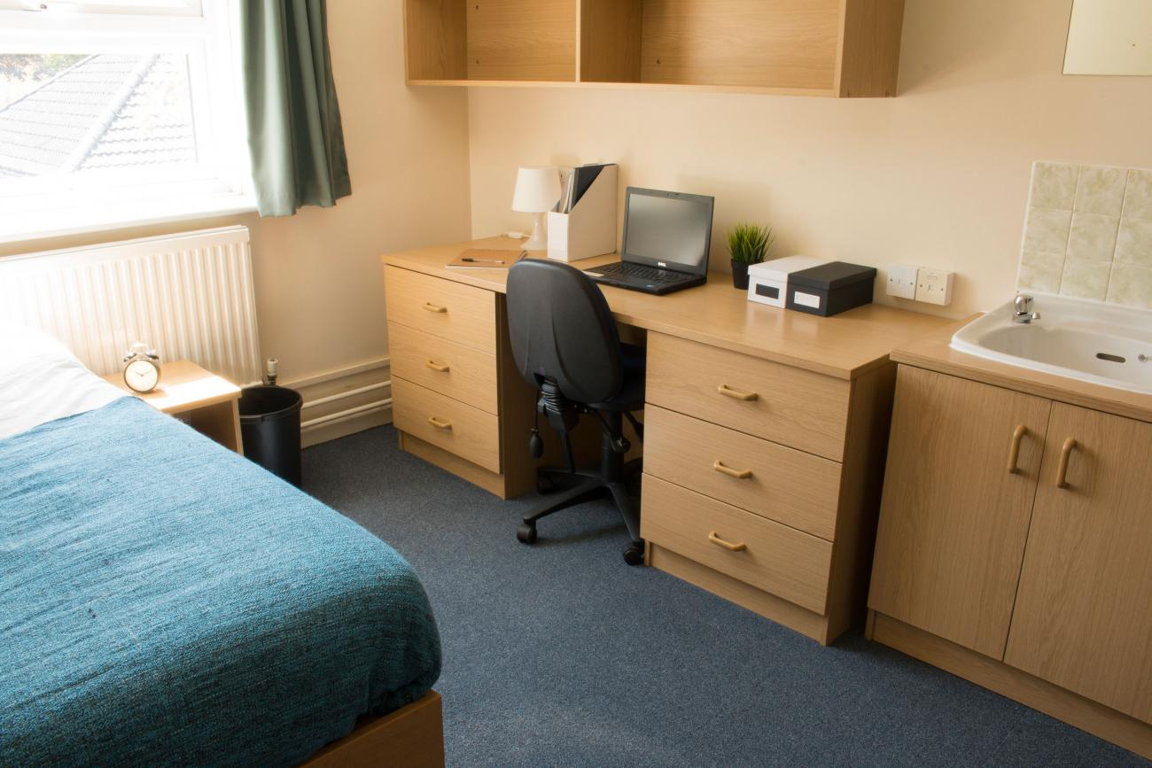 Student bedroom showing a desk and a neatly made bed with dark blue sheets. A large window lets light into the room.
