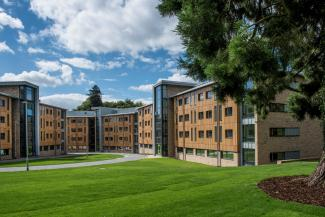Exterior shot of grassy courtyard and student accommodation blocks on a sunny day.